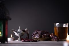 Ramadanvoedsel en drankenconcept Ramadan Lantern met Arabische lamp, houten rozentuin, thee, datafruit en verlichting op een hout stock afbeeldingen