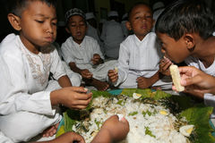 Ramadhan. Children Islamic elementary school students eat together during fasting in living worship in holy month of Ramadan, in Solo, Central Java, Indonesia Stock Photography