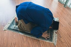 Ramadhan concept stock photo where a muslim man performing solat at his home