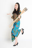 Ramadhan. Full body portrait of happy Southeast Asian woman in batik dress hand holding bamboo oil lamp standing on plain background Stock Photo
