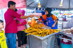 Ramadhan sale 2014. JOHOR, MALAYSIA-JUNE 29: Unidentified traditional roast chicken attends to a customer at Pasar Ramadhan Bukit Gambir on June 29, 2014 in Stock Photo
