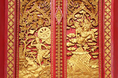 Ramakien表现木雕刻的sclupture在用金叶和红色绘画装饰的天堂森林中间的 免版税库存图片