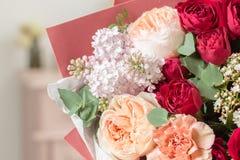 Ramalhete altamente do vermelho colorido grupo luxuoso bonito de flores misturadas na mão da mulher o trabalho do florista na imagens de stock