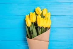 Ramalhete amarelo das tulipas no fundo de madeira azul Fotografia de Stock
