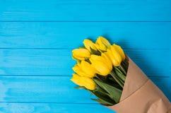 Ramalhete amarelo das tulipas no fundo de madeira azul Imagem de Stock Royalty Free