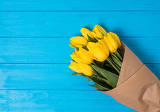 Ramalhete amarelo das tulipas no fundo de madeira azul Imagem de Stock