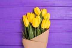 Ramalhete amarelo das tulipas no fundo de madeira roxo Imagens de Stock