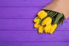 Ramalhete amarelo das tulipas no fundo de madeira roxo Fotografia de Stock Royalty Free