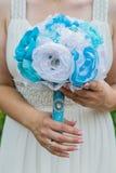 Ramalhete artificial do casamento nas mãos da noiva Imagens de Stock Royalty Free