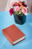 Ramalhete bonito da flor cor-de-rosa no vaso preto na tabela com o caderno velho do vintage no fundo azul de linho Foto de Stock