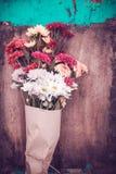 Ramalhete bonito da flor envolvido no papel do ofício no fundo de madeira da tabela imagem de stock