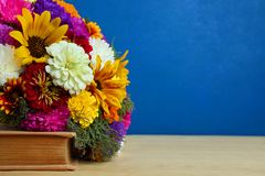 Ramalhete bonito das flores e de um livro Imagem de Stock Royalty Free
