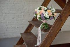 Ramalhete bonito das flores das rosas e de suportes lil?s em uma escada de madeira contra uma parede de tijolo branca foto de stock royalty free