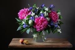 Ramalhete bonito das peônias, das íris e do jasmim no frasco em t Imagens de Stock Royalty Free
