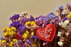 Ramalhete bonito de flores naturais coloridas do jardim do verão - perezii do Limonium, com o coração vermelho fotos de stock royalty free
