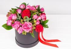 Ramalhete bonito de rosas cor-de-rosa e vermelhas e da fita vermelha em um circula fotos de stock