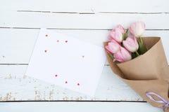 Ramalhete bonito de tulipas cor-de-rosa ao lado de um envelope branco e de corações cor-de-rosa do açúcar Foto de Stock