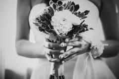 Ramalhete bonito do casamento da fotografia branca preta das flores nas mãos a noiva Fotos de Stock Royalty Free