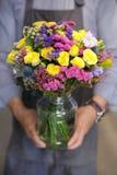 Ramalhete bonito em cores amarelas, cor-de-rosa, azuis das rosas, em statice e em outras flores nas mãos masculinas do florista imagens de stock