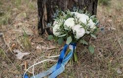 Ramalhete branco do casamento do casamento com as fitas azuis de seda apoiadas na árvore imagens de stock royalty free