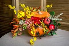 Ramalhete brilhante do outono em uma abóbora no fundo escuro imagens de stock royalty free