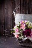 Ramalhete cor-de-rosa dos gillyflowers e do alstroemeria na cesta sobre Imagem de Stock Royalty Free