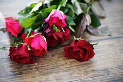 Ramalhete cor-de-rosa vermelho da flor/rosa e amor do dia de Valentim de rosas vermelhas na tabela de madeira imagem de stock