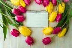 Ramalhete da tulipa e papel cor-de-rosa e amarelos do balnk no fundo de madeira, espaço da cópia Fotografia de Stock