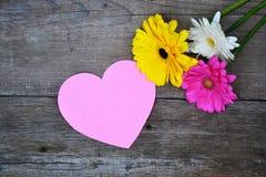 Ramalhete das flores com coração de papel cor-de-rosa na madeira Fotos de Stock