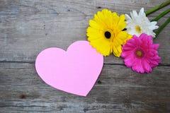 Ramalhete das flores com coração de papel cor-de-rosa na madeira Foto de Stock