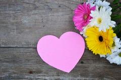 Ramalhete das flores com coração de papel cor-de-rosa na madeira Imagem de Stock Royalty Free