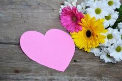 Ramalhete das flores com coração de papel cor-de-rosa na madeira Fotos de Stock Royalty Free