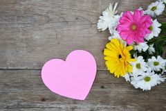 Ramalhete das flores com coração de papel cor-de-rosa na madeira Foto de Stock Royalty Free
