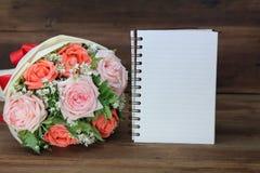 Ramalhete das flores cor-de-rosa e de um livro branco no fundo de madeira para felicitações foto de stock