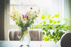 Ramalhete das flores em um vaso de vidro na tabela na frente de uma janela com uma cadeira Decoração Home fotos de stock