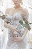 Ramalhete das flores em um vaso que guarda uma noiva da menina em um vestido de casamento branco elegante com um anel grande em s fotografia de stock royalty free