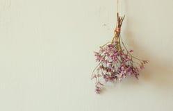 Ramalhete das flores secadas que penduram na corda contra o fundo de madeira Fotos de Stock Royalty Free
