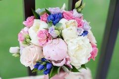 Ramalhete das rosas e as peônias e as alianças de casamento fotos de stock royalty free