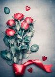 Ramalhete das rosas vermelhas com fita e corações no fundo cinzento do desktop, vista superior Disposição para o dia de Valentim, imagem de stock