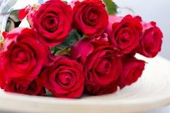 ramalhete das rosas vermelhas que encontram-se em uma placa Fotos de Stock Royalty Free