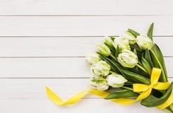 Ramalhete das tulipas brancas decoradas com a fita amarela no fundo de madeira branco Imagem de Stock