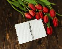 Ramalhete das tulipas, caderno vazio, pena no fundo de madeira Imagem de Stock