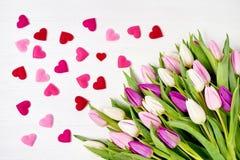 Ramalhete das tulipas com corações cor-de-rosa no fundo de madeira branco Vista superior, espaço da cópia Foto de Stock Royalty Free