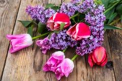 Ramalhete das tulipas com o lilás no fundo de madeira Fotos de Stock