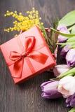 Ramalhete das tulipas e de um presente em um fundo de madeira Foto de Stock