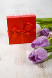 Ramalhete das tulipas e de um presente em um fundo de madeira Fotografia de Stock
