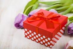 Ramalhete das tulipas e de um presente em um fundo de madeira Foto de Stock Royalty Free
