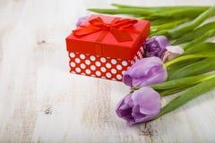 Ramalhete das tulipas e de um presente em um fundo de madeira Fotos de Stock Royalty Free
