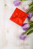 Ramalhete das tulipas e de um presente em um fundo de madeira Fotos de Stock