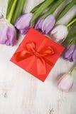 Ramalhete das tulipas e de um presente em um fundo de madeira Imagem de Stock Royalty Free